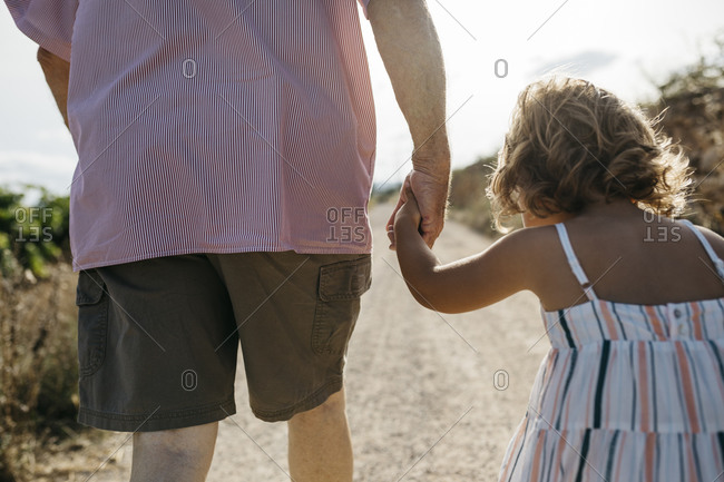 Close-up of grandfather holding granddaughter's hand while walking on dirt road