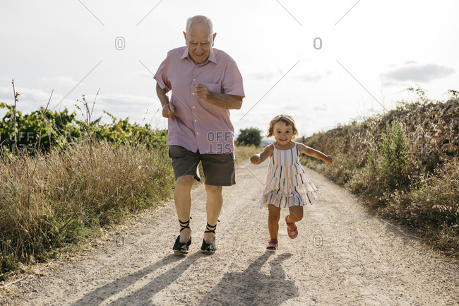 Playful senior man running with granddaughter on dirt road amidst plants
