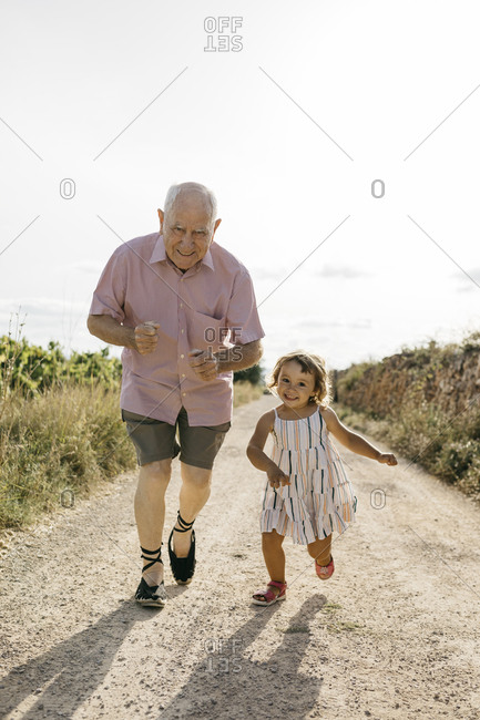 Playful senior man running with granddaughter on dirt road amidst plants during sunny day