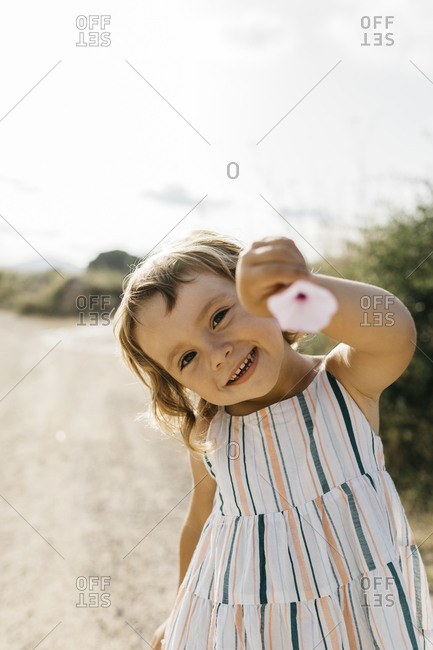 Close-up of happy girl showing flower while standing against sky during sunny day