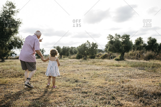 Grandfather with granddaughter walking on grassy land against sky