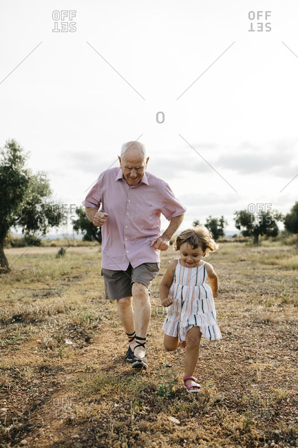 Playful grandfather with granddaughter running on land against sky