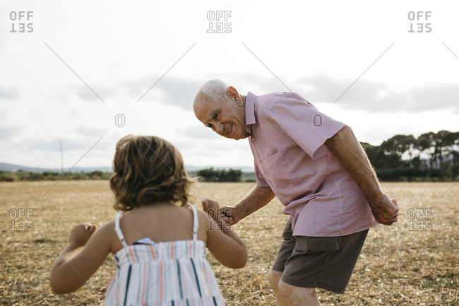 Grandfather looking at granddaughter while standing on land against sky