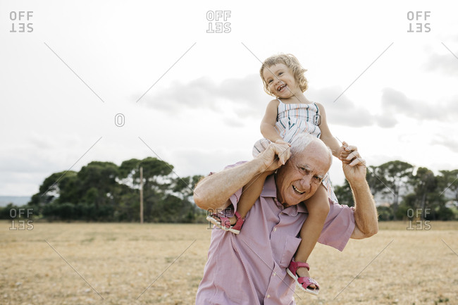 Happy grandfather carrying granddaughter on shoulders while standing against sky