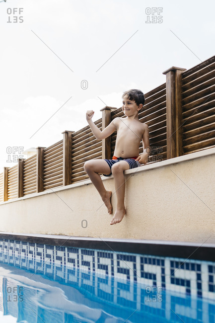Boy flexing muscles while sitting at poolside