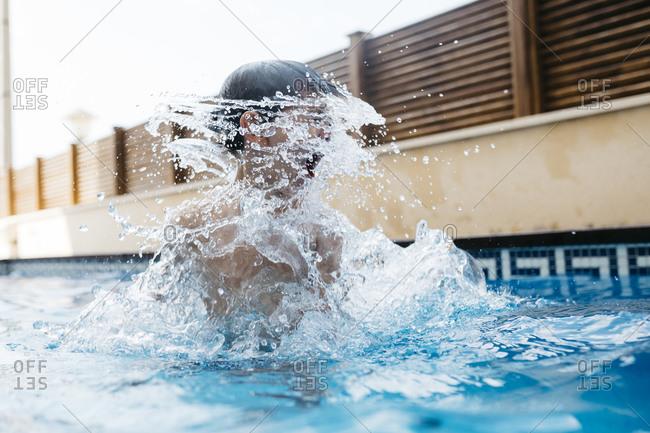 Boy splashing water around face in pool during summer