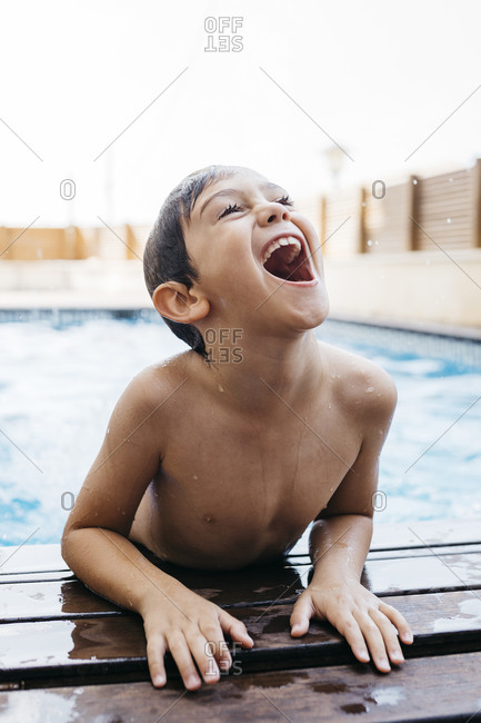 Cheerful boy moving up at poolside