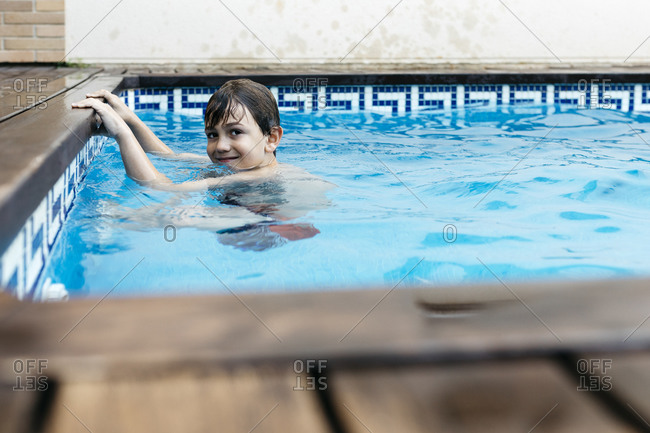 Boy learning how to swim at poolside