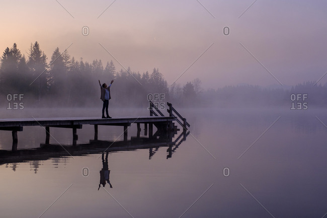 Woman standing with raised arms on lakeshore jetty at foggy dawn