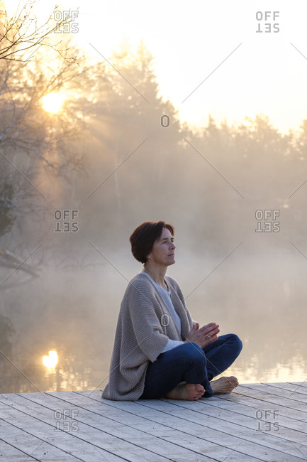 Adult woman meditating on lakeshore jetty at foggy sunrise