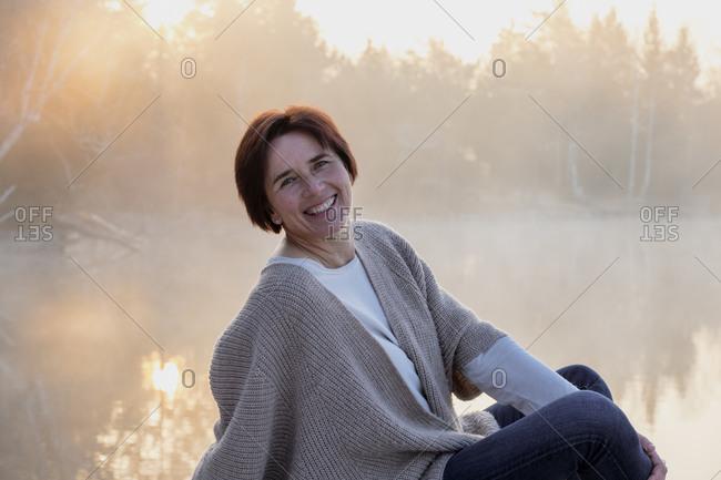Portrait of adult woman posing on lakeshore at foggy sunrise