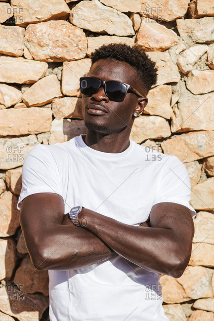 Close-up of young man wearing sunglasses with arms crossed standing against stone wall