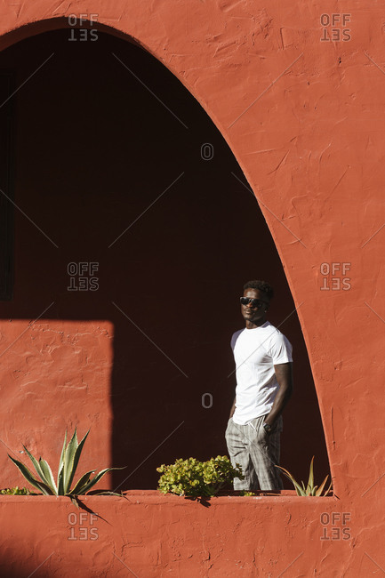 Young man wearing sunglasses standing by red wall during sunny day
