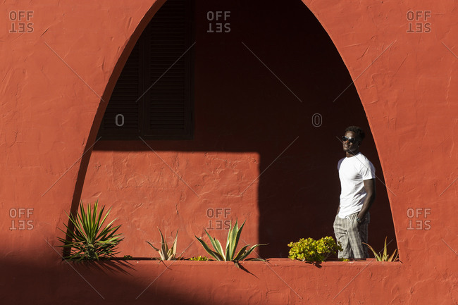 African young man wearing sunglasses standing by red wall during sunny day