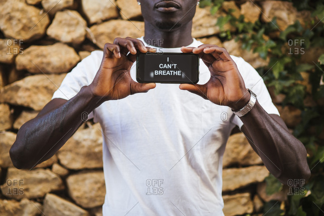 Close-up of young man showing text over smart phone against stone wall