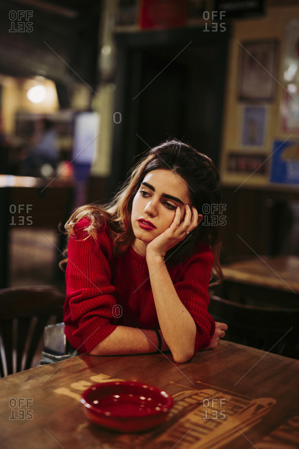 Sad thoughtful mid adult woman with hand on chin sitting at table in restaurant