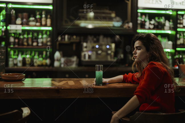 Thoughtful woman with drink on bar counter sitting in restaurant