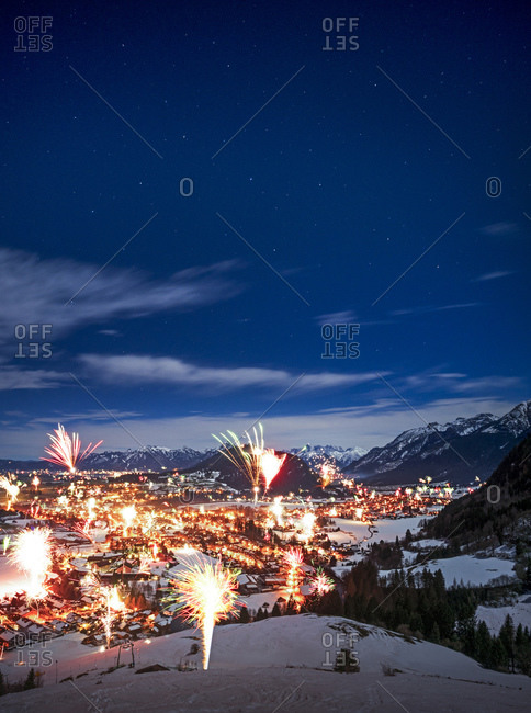 Germany- Bavaria- Edelsberg- Fireworks exploding over mountain town during New Years Eve