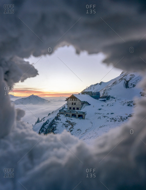 Secluded mountain hut seen through hole in snow