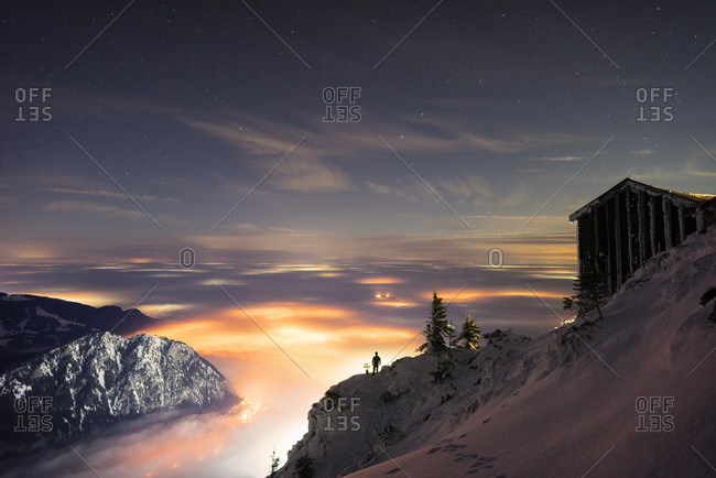 Secluded mountain hut at dusk with illuminated valley in background