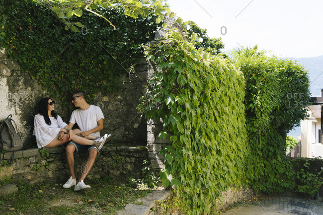 Young couple in love sitting on bench- Bellagio- Italy
