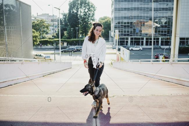 Beautiful woman walking with dog on elevated walkway