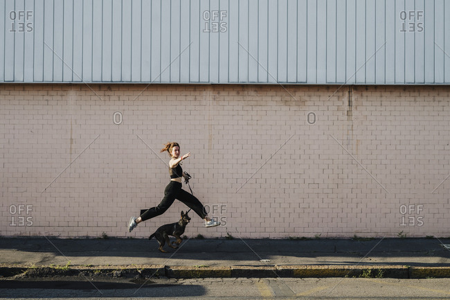 Woman running with dog at sidewalk against wall