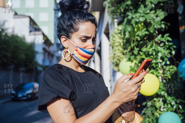 Worried woman using phone while wearing mask in city