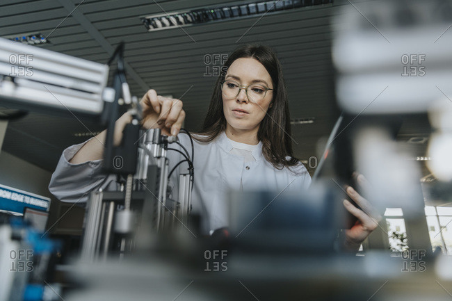 Young female scientist examining machinery in laboratory