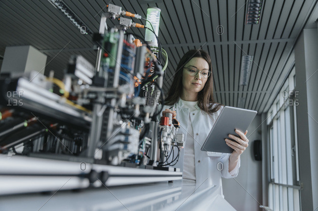 Young woman using digital tablet while standing by machinery in laboratory