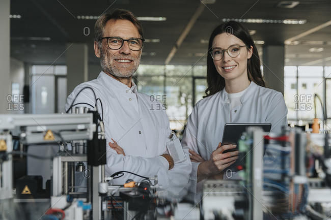 Smiling male and female scientists standing by machinery in laboratory