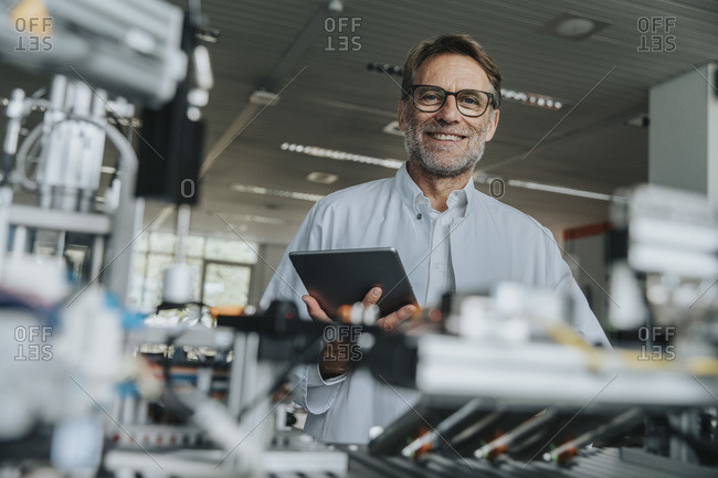 Smiling male scientist holding digital tablet while standing by machinery in laboratory