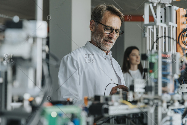Mature man examining machinery with female colleague in background at laboratory