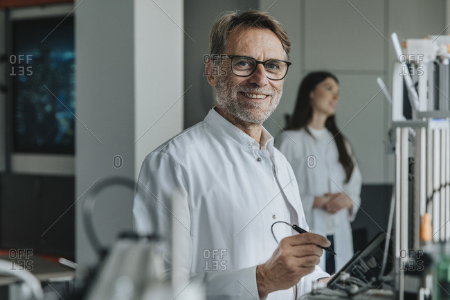 Scientist inventing machinery with female colleague in background at laboratory