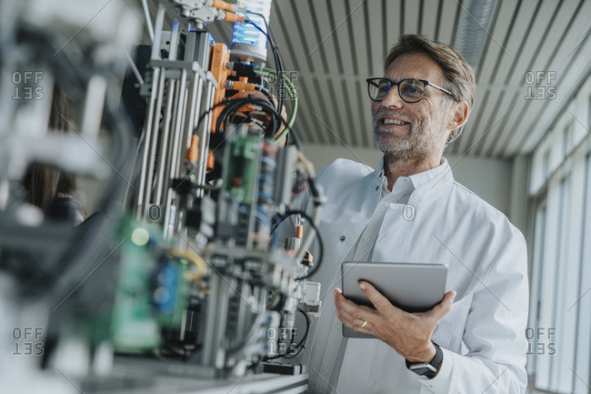Smiling male scientist holding digital tablet examining machinery in laboratory