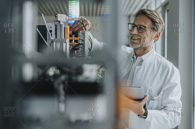 Smiling male scientist holding digital tablet inventing machinery in laboratory