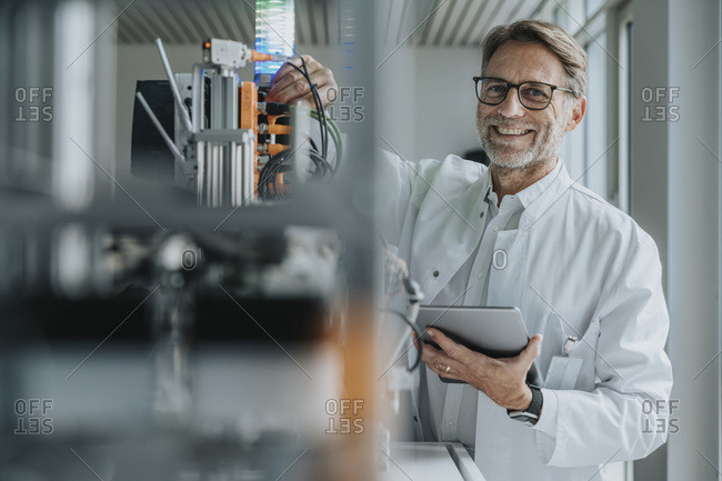 Smiling mature man with digital tablet inventing machinery in laboratory