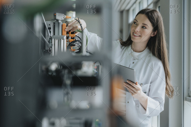 Smiling female scientist holding digital tablet inventing machinery in laboratory