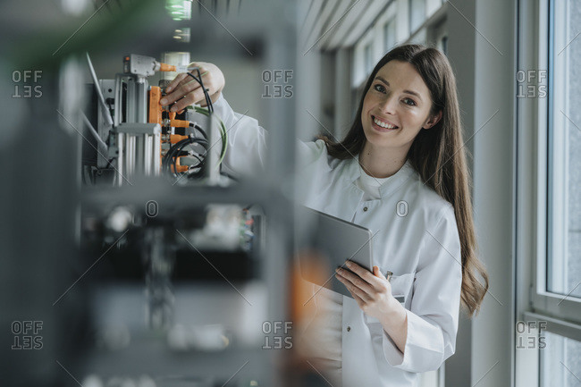 Smiling female scientist holding digital tablet inventing machinery in factory