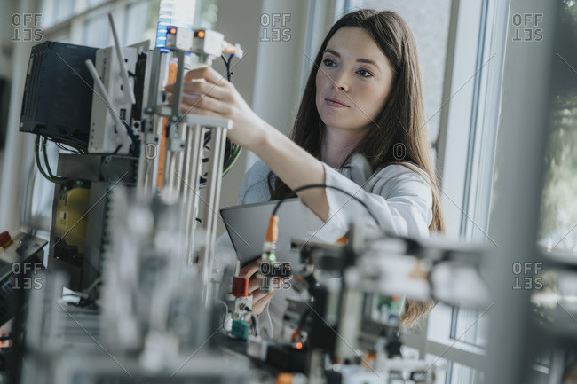 Confident female engineer inventing machinery in laboratory