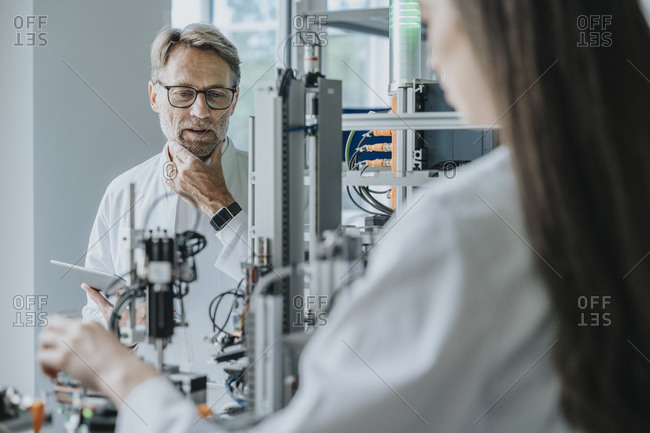 Thoughtful male scientist looking at machinery while working with female colleague in laboratory
