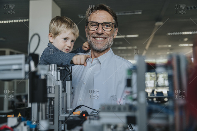 Scientist father showing machinery to son in laboratory at factory