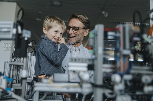 Smiling male scientist showing machinery to son in laboratory at factory