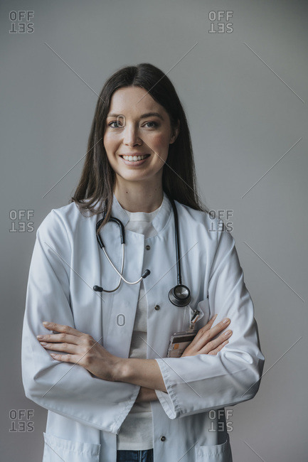 Smiling female doctor with arms crossed standing against wall in hospital
