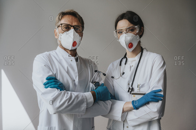 Doctors wearing masks with arms crossed standing against wall in hospital