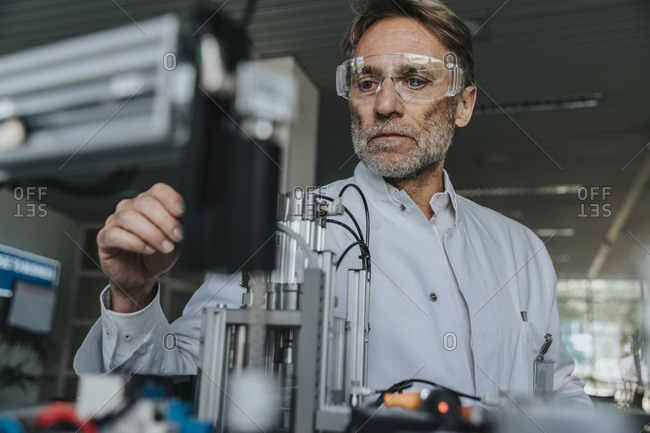 Male scientist with protective eyewear examining machine in laboratory