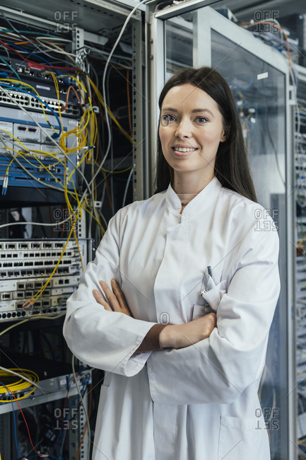 Female IT professional with arms crossed standing in server room