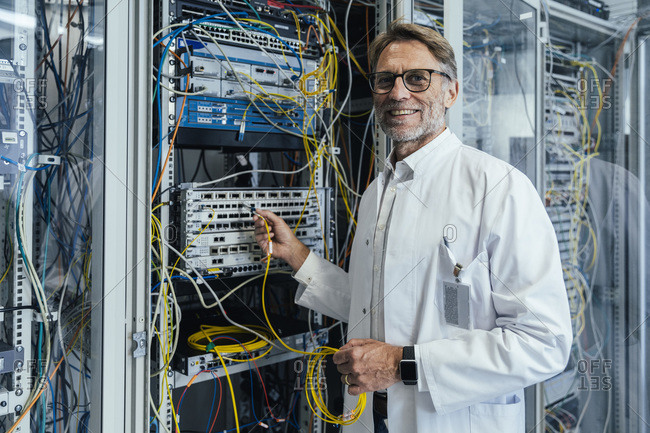 Smiling mature man plugging transceiver on fiber optic cable in data center