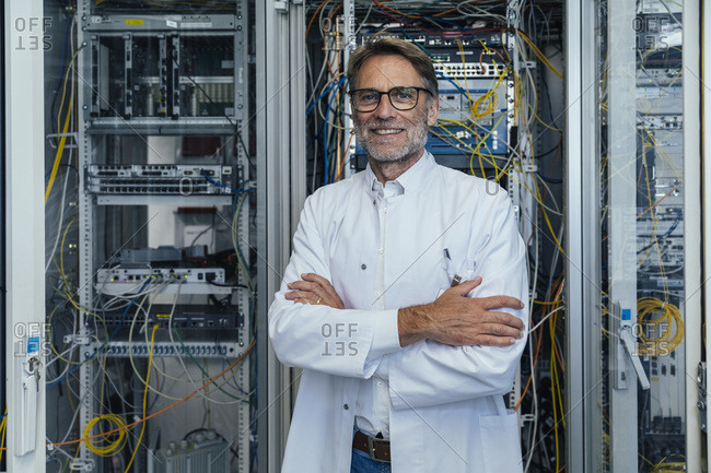 Smiling mature man with arms crossed standing in server room