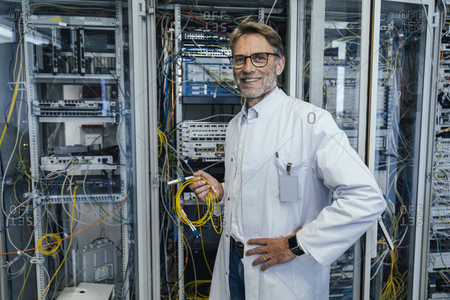 Male IT professional holding cables while standing in data center
